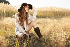 Sentada modelo hermosa de la señora joven en campo en la salida del sol Imagenes de archivo