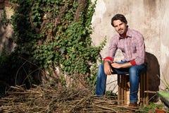 Sentada modelo masculina con las piernas cruzadas imagen de archivo libre de regalías