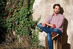 Sentada modelo masculina con las piernas cruzadas imágenes de archivo libres de regalías