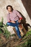 Sentada modelo masculina con las piernas cruzadas fotografía de archivo
