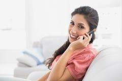 Sentada morena contenta en su sofá en el teléfono que mira la leva Imagen de archivo libre de regalías