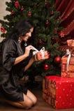 Sentada morena feliz cerca de un árbol de navidad con los regalos Foto de archivo libre de regalías