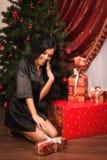 Sentada morena feliz cerca de un árbol de navidad con los regalos Fotos de archivo