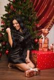 Sentada morena feliz cerca de un árbol de navidad con los regalos Fotografía de archivo