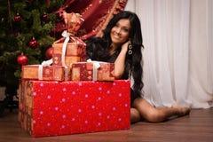 Sentada morena feliz cerca de un árbol de navidad con los regalos Fotografía de archivo libre de regalías