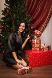 Sentada morena feliz cerca de un árbol de navidad con los regalos Imágenes de archivo libres de regalías