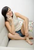 Sentada morena joven en el sofá con el teléfono Imagen de archivo