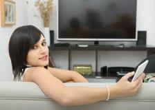 Sentada morena joven en el sofá con el teléfono Fotos de archivo