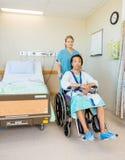 Sentada paciente masculina en la silla de ruedas mientras que enfermera Imagenes de archivo