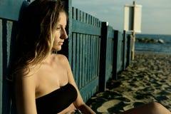 Sentada pensativa de la mujer rubia joven triste sola en la playa en la puesta del sol Imagen de archivo libre de regalías