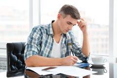 Sentada pensativa hermosa y dibujo del hombre en oficina Fotografía de archivo
