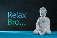 Sentada relajada y el meditar de la estatuilla de Buda, haciendo exersice de la yoga Relaje el bro - inscripción foto de archivo