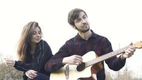 Sentada romántica y hombre de los pares que tocan la guitarra para la novia outdoor metrajes