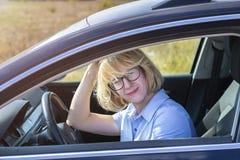 Sentada rubia de la mujer detrás de la rueda del coche imagenes de archivo