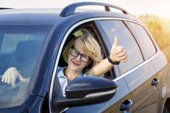 Sentada rubia de la mujer detrás de la rueda del coche foto de archivo