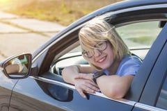 Sentada rubia de la mujer detrás de la rueda del coche fotos de archivo