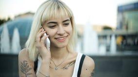 Sentada rubia joven de la mujer, hablando en el teléfono, sonrisa, mirando la cámara almacen de metraje de vídeo