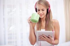 Sentada rubia joven en la cama que escucha el te de la música y de la bebida Imagenes de archivo