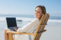 Sentada rubia magnífica en silla de cubierta usando el ordenador portátil en la playa Imagen de archivo libre de regalías