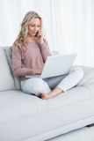 Sentada rubia sonriente en el sofá usando el ordenador portátil imagen de archivo libre de regalías