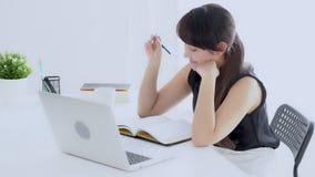 Sentada sonriente de la mujer asiática hermosa en el estudio de la sala de estar y aprendizaje escribiendo el cuaderno en casa, p metrajes