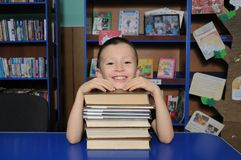 Sentada sonriente del muchacho en la biblioteca, poniendo la cabeza en la pila de libro fotos de archivo libres de regalías