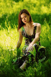 Brunette que se sienta en hierba verde imagen de archivo libre de regalías