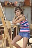 Sentada triguena joven en la base de los pintores Foto de archivo