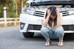 Sentada triste de la sensación asiática joven de la mujer cerca del coche analizado Fotografía de archivo libre de regalías