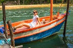 Sentada turística de la chica joven en un barco de pesca tailandés Naturaleza foto de archivo libre de regalías