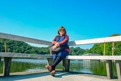 Sentada turística de las mujeres mayores en la silla de piedra al lado del lago encima de la montaña Foshan del xiqiao fotos de archivo libres de regalías