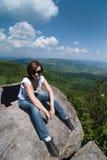 Sentada turística femenina en la roca Fotos de archivo