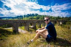Sentada turística joven en el puente ferroviario de piedra viejo cercano al aire libre de la colina verde Imagen de archivo