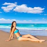 Sentada turística morena en broncear de la arena de la playa feliz Foto de archivo libre de regalías