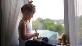 Sentada y alimentaciones de la muchacha el oso almacen de metraje de vídeo