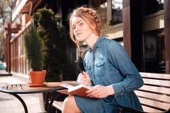 Sentada y escritura bonitas de la mujer en cuaderno al aire libre Foto de archivo