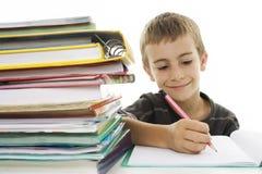 Sentada y escritura del muchacho de escuela en cuaderno. Imagen de archivo libre de regalías