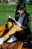 Sentada y lectura de la chica joven un libro en un día de primavera soleado y hermoso en el parque en un banco Fotos de archivo libres de regalías