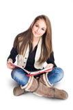 Sentada y lectura jovenes lindas de la muchacha del estudiante. Imagen de archivo
