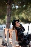 Sentada y magro de la mujer joven en el banco Fotos de archivo libres de regalías