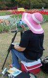 Sentada y pintura de la señora del artista al aire libre. Foto de archivo