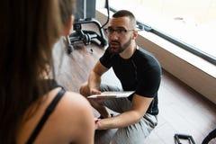 Sentada y reclinación de la mujer de Takes Notes While del instructor fotografía de archivo libre de regalías