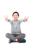 Sentada y sonrisas jovenes del muchacho sobre blanco imagenes de archivo