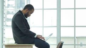 Sentada y trabajos africanos del hombre de negocios sobre el ordenador portátil almacen de metraje de vídeo