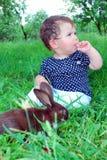 Sentando en la hierba a una niña, y por su conejo negro. Fotos de archivo