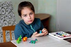Sentando en la tabla a una niña que esculpe del plasticine imagen de archivo