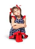 Sentando a menina triste, pensativa da criança com as curvas do vermelho, isoladas no wh Foto de Stock