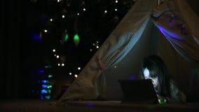 Sentando-se em casa em uma barraca na perspectiva de uma árvore de Natal, uma menina que encontra-se no assoalho que fala no víde vídeos de arquivo