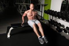 Sentar-UPS que hace masculino en un gimnasio Imagenes de archivo