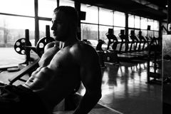 Sentar-UPS que hace masculino en un gimnasio Imagen de archivo libre de regalías